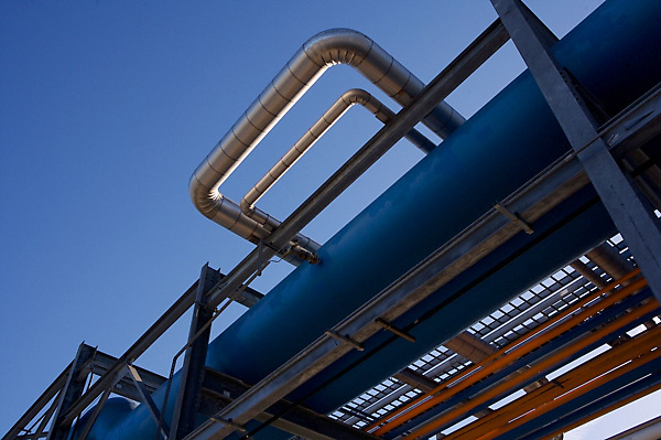 Stock photo of pipes along an elevated outdoor walkway at a chemical plant
