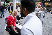 Fascinating character with hair in pigtails watches a street performer singing in the Bull Ring shopping district on 3rd August 2021 in Birmingham, United Kingdom.
