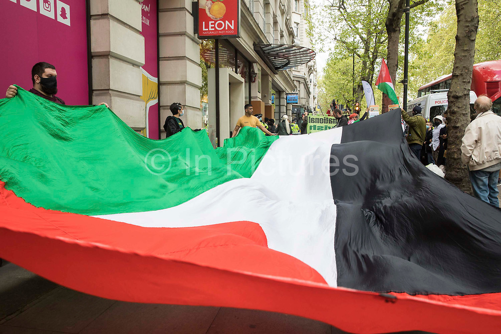Activists from Palestine Action protest with a huge Palestinian flag outside the UK headquarters of Elbit Systems, an Israel-based company developing technologies used for military applications including drones, precision guidance, surveillance and intruder-detection systems, on 11th May 2021 in London, United Kingdom. The activists were protesting against the companys presence in the UK and in solidarity with the Palestinian people at a time of a significant rise in tension in Israel and the Occupied Territories following attempts at forced evictions of Palestinian families in the Sheikh Jarrah neighbourhood of East Jerusalem, the deployment of Israeli forces at the Al-Aqsa mosque and the killing of children in Gaza.