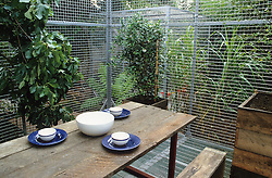 Wooden table and bench surrounded by metal 'cage'.