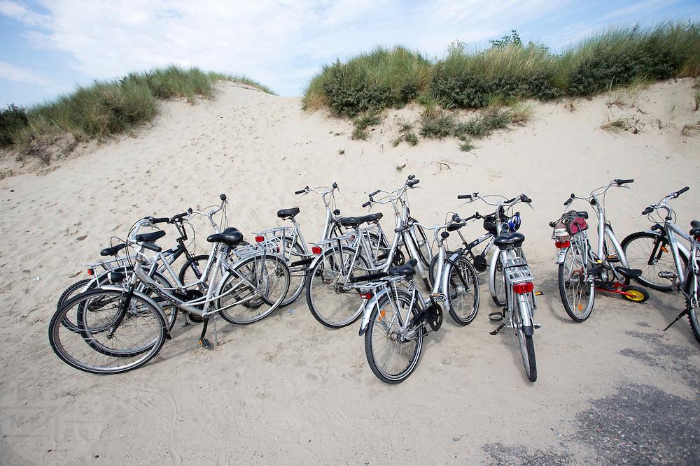 Aan de duin bij het strand van de Brouwersdam staan fietsen geparkeerd.<br /> <br /> On the dunes at the beach of the Brouwersdam bicycles parked.