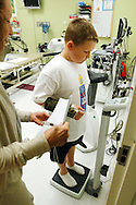 Zachary Frantzen, 10, (R) is weighed by Marilyn Day director of the Shapedown Program at The Children's Hospital in Aurora, Colorado July 8, 2010.  The program is part of the child and teen weight management program at the hospital. REUTERS/Rick Wilking (UNITED STATES)