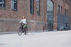 Young woman riding a bicycle in front of brick wall, Munich, Bavaria, Germany