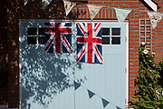 As the Coronavirus lockdown continues over the May Bank Holiday, the nation commemorates the 75th anniversary of VE Day Victory in Europe Day, the day that Germany officially surrendered in 1945 and in Dulwich, neighbours and residents emerge from their homes to party while still observing social distancing rules. Union Jack flags hang from a garage door, on 8th May 2020, in London, England.