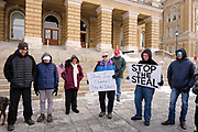 "02 JANUARY 2021 - DES MOINES, IOWA: Supporters of President Donald Trump pray in front of the Iowa State Capitol. About 30 people marched around the Iowa State Capitol Saturday afternoon to protest the outcome of the November 3 general election in the United States. They are a part of the ""Stop the Steal"" movement which maintains that the election was stolen from Donald Trump by massive voter fraud. There is no evidence supporting their conspiracy theory. This is the 9th week Donald Trump supporters have marched around the Capitol. They've been there every week since the Nov. 3 election. More than 1,000 people showed up the first week, but the crowd has gotten smaller every week.      PHOTO BY JACK KURTZ"