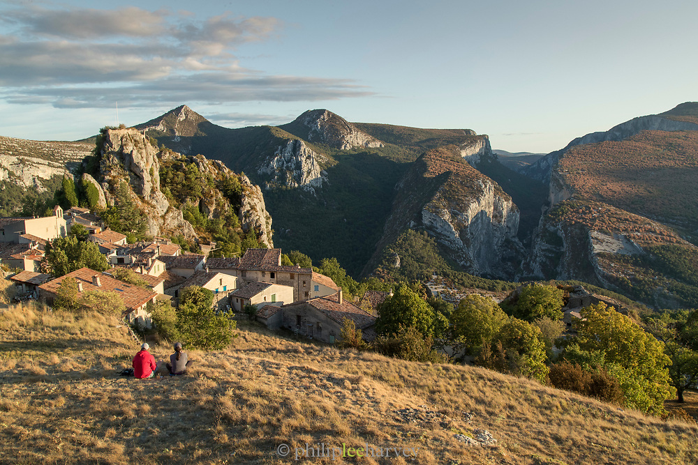 Couple sitting on field above village of Rougon overlooking the Gorges du Verdon, France