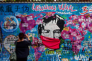 A woman taking a photograph at the Prague Lennon Wall in-front of a John Lennon graffiti. Once a normal wall, since the 1980s it has been filled with John Lennon-inspired graffiti and pieces of lyrics from Beatles' songs. The Czech government lowered the security measures and as of Monday 25 May 2020, wearing of protective masks will be mandatory only in the interiors of buildings other than the place of residence and in public transport.