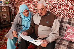 Asian carer reading with elderly Asian man at home, ***NOT TO BE USED IN THE EAST MIDLANDS***