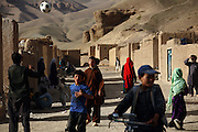 Afghans are walking near their homes in a rocky village located near Bamyian's archaeological site. The cliff where once stood the Western Buddha (55m - 'Male') is photographed after sunset in Bamiyan, Afghanistan, an area mostly populated by Hazaras. The Buddhas of Bamiyan were two 6th century monumental statues of standing Buddhas carved into the side of a cliff in the Bamiyan valley in the Hazarajat region of central Afghanistan, situated 230 km northwest of Kabul at an altitude of 2500 meters. The statues represented the classic blended style of Gandhara art. The main bodies were hewn directly from the sandstone cliffs, but details were modelled in mud mixed with straw, coated with stucco. Amid widespread international condemnation, the smaller statues (55 and 39 meters respectively) were intentionally dynamited and destroyed in 2001 by the Taliban because they believed them to be un-Islamic idols. Once a stopping point along the Silk Road between China and the Middle East, researchers think Bamiyan was the site of monasteries housing as many as 5,000 monks during its peak as a Buddhist centre in the 6th and 7th centuries. It is now a UNESCO Heritage Site since 2003. Archaeologists from various countries across the world have been engaged in preservation, general maintenance around the site and renovation. Professor Tarzi, a notable An Afghan-born archaeologist from France, and a teacher in Strasbourg University, has been searching for a legendary 300m Sleeping Buddha statue in various sites between the original standing ones, as documented in the old account of a renowned Chinese scholar, Xuanzang, visiting the area in the 7th century. Professor Tarzi worked on projects to restore the other Bamiyan Buddhas in the late 1970s and has spent most of his career researching the existence of the missing giant Buddha in the valley.
