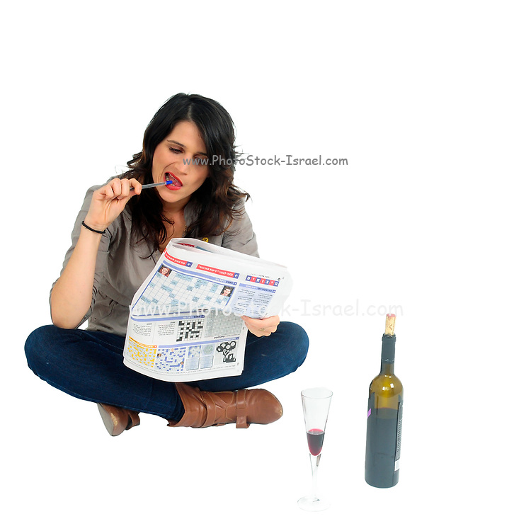 young woman drinks red wine while reading a newspaper studio shot on white background