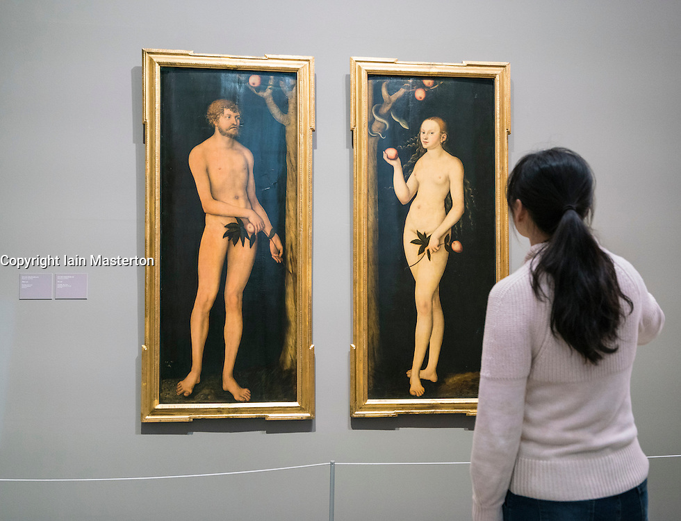 Visitor looking at paintings Adam and Eve by Lucas Cranach at Gemäldegalerie Alte Meister or Zwinger Museum in Dresden, Germany .Editorial Use Only.