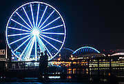 "A couple enjoys a mild night on Pier 62 and 63 in Seattle as the Great Wheel and CenturyLink Field glow turquoise to raise awareness of lung disease as the American Lung Association of the Mountain Pacific kicks off National Women's Lung Health Week with a ""Turquoise Takeover."" <br />