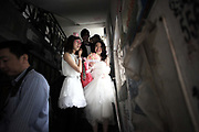 Juan Juan, the bride to be, leaves her home accompanied by the maid of honor on her way to the church to be married to Coca Dai in Shanghai, China on 23 May 2009. A hip street artist and a recent Catholic convert, Mr. Dai is one of many young Chinese embracing religion, perhaps to fill the lack of belief and ideology in an authoritarian communist China that embraces the most extreme form of capitalism in practice. The Chinese government and the Vatican have a long history of simmering mutual distrust and suspicion, as two parties compete for the control of the Chinese Catholic church, with some 15 million and growing number of faithfuls.  Overall Christians now number over 110 million in China, which makes it the third largest Christian nation in the world.