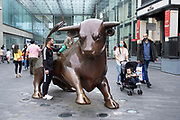With most shops now open but with retail sales suffering due to the Coronavirus pandemic, shoppers wearing face masks, which became compulsory in shops on the 24th July, pass Bully, the Bull Ring shopping centre bull while out shopping in the city centre on 5th August 2020 in Birmingham, United Kingdom. Coronavirus or Covid-19 is a respiratory illness that has not previously been seen in humans. While much or Europe has been placed into lockdown, the UK government has put in place more stringent rules as part of their long term strategy, and in particular social distancing.