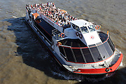 """Tourists approach London Bridge on a """"City Cruises"""" boat, along the River Thames, on a beautiful late September afternoon"""