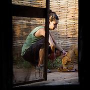 On a strictly hush hush basis at a time of hardship, Peace Corps volunteer gives her dog Yoda a tasty meat treat behind her hut. Koumbadiouma, Kolda, Senegal.