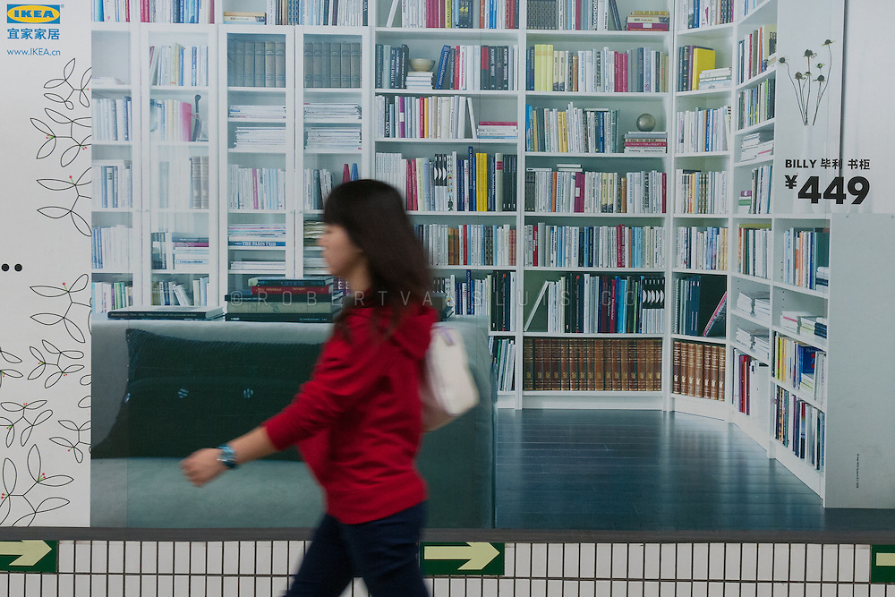 Young woman walking past an IKEA poster in the Beijing underground, Beijing, China