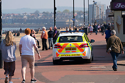 Portobello, Scotland, UK. 25 April 2020. Views of people outdoors on Saturday afternoon on the beach and promenade at Portobello, Edinburgh. Good weather has brought more people outdoors walking and cycling. Police are patrolling in vehicles but not stopping because most people seem to be observing social distancing. Police patrol car on promenade.  Iain Masterton/Alamy Live News