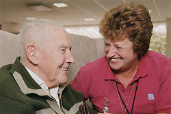 Elderly man and female clinic assistant laughing,