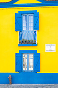Brightly coloured blue and yellow facade, balconies, shutters, hydrant in Cais dos Botiroes by the marina at Aveiro, Portugal