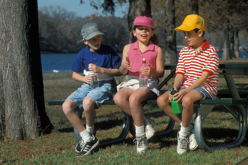 Two Anglo boys and one Anglo girl sit and talk on bench outside while wearing hats and drinking water to protect from the Texas sun.  Model Release.<br /> ©Bob Daemmrich