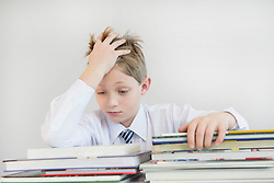 Frustrated boy with stack of books, close up