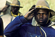 "A group of young juvenile (criminal)  offenders participate in an ""open prison"" rehabilitation programme designed to build self esteem, courage, purposeful lives, seen here seen saluting early in the morning before beginning the day's activities. They are known as ""Buffalo soldiers"" and use the same clothing as Gral Custer and his cavalry used in the American civil war. Most of  the offenders are black, USA. This programme runs by the name of Vision Quest's Wagon Train."
