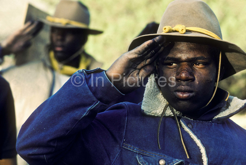"""A group of young juvenile (criminal)  offenders participate in an """"open prison"""" rehabilitation programme designed to build self esteem, courage, purposeful lives, seen here seen saluting early in the morning before beginning the day's activities. They are known as """"Buffalo soldiers"""" and use the same clothing as Gral Custer and his cavalry used in the American civil war. Most of  the offenders are black, USA. This programme runs by the name of Vision Quest's Wagon Train."""
