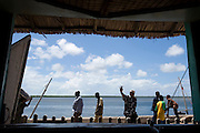 Men walking by on seafront seen through window in Lamu, Kenya.