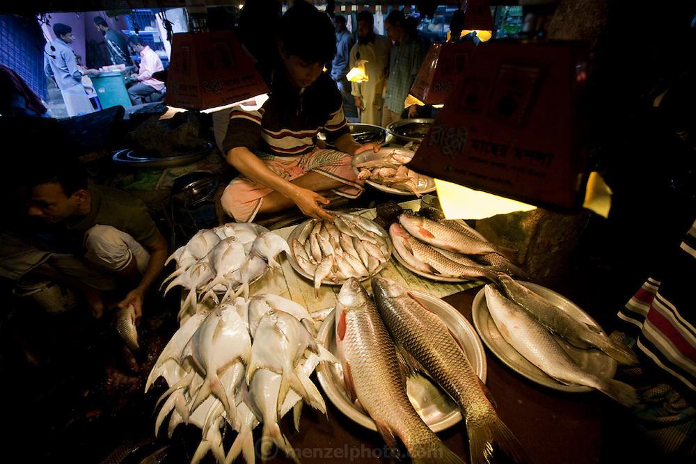 A vendor sorts fish at the Santinagar Market  in Dhaka, Bangladesh.
