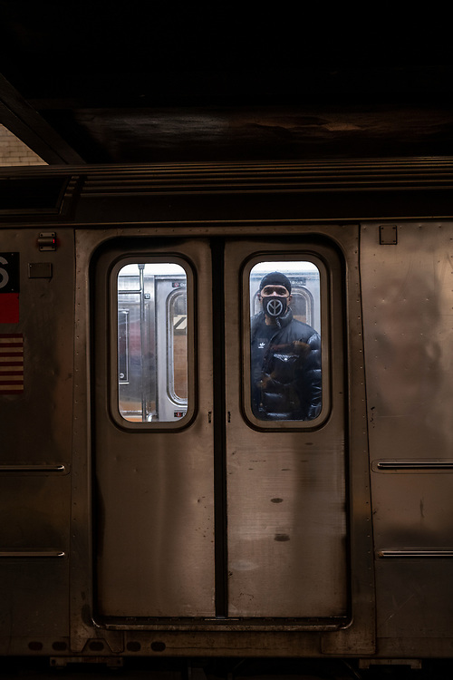 New York City, USA - March 18, 2020: A solitary man wearing a protective mask stands inside a subway car about to depart 181st Street Station in Manhattan.