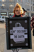 A female campaigner from Extinction Rebellion during a Black Friday protest at Oxford Circus on the 29th November 2019 in central London in the United Kingdom. Black Friday is a shopping event that originated from the US where retailers cut prices on the day after the Thanksgiving holiday. Extinction Rebellion are calling to boycott fashion and excessive consumerism.