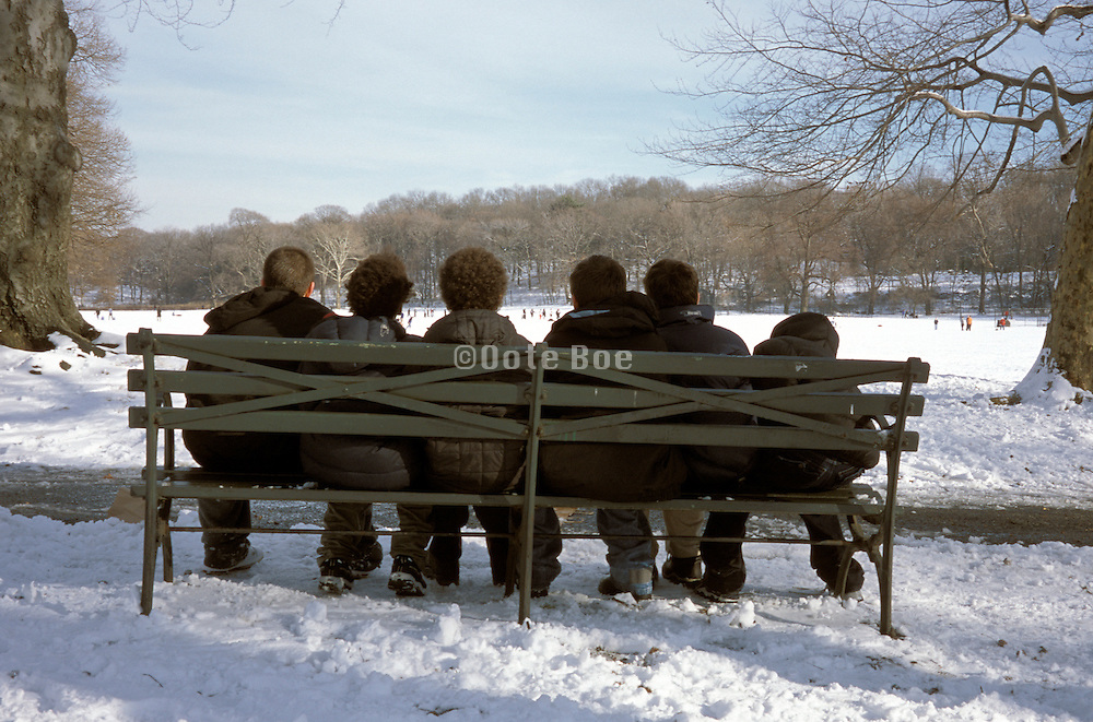 young boys seated on city park bench