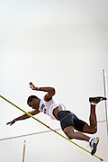 An Illinois College pole vaulter at the apex of his jump glances down after clearing the bar during the Midwest Conference Championships on Friday.