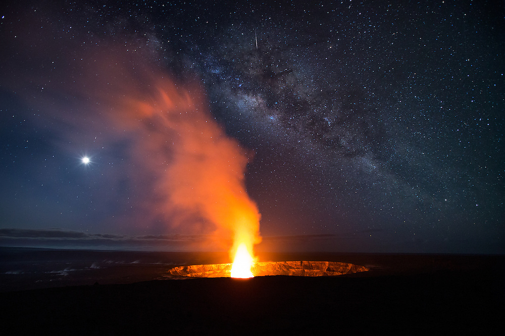 The Milky Way and moon glow brightly in the sky above the fiery pit of Halema'uma'u, as a meteor streaks through the heavenly scene