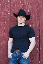 Portrait of a rugged All American cowboy in a black tee shirt leaning against a rustic barn