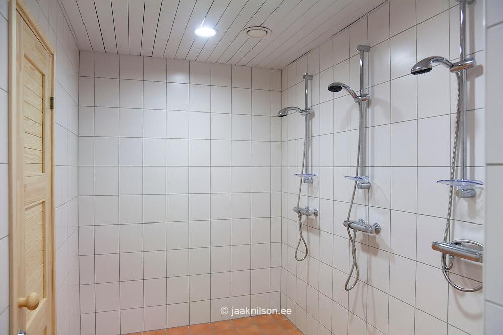 Shower room, tiled in white tiles, with three showers. Door. Metsapoole school, Estonia
