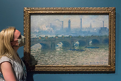 """© Licensed to London News Pictures. 04/08/2020. LONDON, UK. A staff member poses with """"Waterloo Bridge, Overcast"""", 1903, by Claude Monet. Preview of """"Gauguin and the Impressionists : Masterpieces from the Ordrupgaard Collection"""" at the Royal Academy of Arts in Piccadilly.  60 works from a collection of Impressionist paintings, assembled by wealthy Danish couple Wilhelm and Henny Hansen, are on show 7 August to 18 October 2020, and includes masterpieces by Gauguin, Degas, Monet, Morisot, Pissarro, Renoir and Sisley.  Photo credit: Stephen Chung/LNP"""