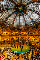 A trampoline suspended below the stained glass dome (and above, to the right, the Glass Walk) of Galeries Lafayette Paris Haussmann department store, Paris, France.