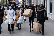 Shoppers return to Oxford Street as non-essential shops reopen and the national coronavirus lockdown three eases on 12th April 2021 in London, United Kingdom. Now that the roadmap for coming out of the national lockdown has been laid out, this is the first phase of the easing of restrictions, and large numbers of people are out in Londons retail district laden with shopping bags.