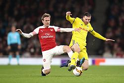 Arsenal's Nacho Monreal (left) and FC BATE Borisov's Nemanja Milic battle for the ball during the UEFA Europa League round of 32 second leg match at the Emirates Stadium, London.