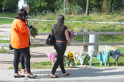 © Licensed to London News Pictures 21/09/2021. <br /> Kidbrooke, UK, Three of Sabina's friends arrive to lay flowers at the scene. A large police cordon is still in place around Cator Park at Kidbrooke Village in Kidbrooke, South East London today after the body of 28 year old school teacher Sabina Nessa was found near a community centre. Police believe Sabina was murdered by a stranger. Photo credit:Grant Falvey/LNP