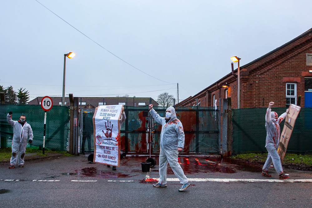 Activists take radical action at Napier Barracks to highlight human rights violations on the 28th of January 2021 in Folkestone, United Kingdom. Activists dressed in white suits and masks, throw buckets of fake blood through the gates of Napier Barracks to send a clear message to Priti Patel and the Home office. Close Napier camp or there will be blood on your hands Following ongoing concerns over the poor living conditions at Napier barracks, and the failures in handling the inevitable Covid-19 outbreak onsite, pressure has been mounting on the Home Office to close the camp. (photo by Andy Aitchison)