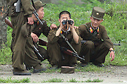 North Korean soldiers keep watch from the town of Sunuiju on the DRPK-China border July 9, 2006. North Korea promised to use force against any country that tries to pressure it into a halt of its missile launches. DPRK, north korea, china, dandong, border, liaoning, democratic, people's, rebiblic, of, korea, nuclear, test, rice, japan, arms, race, weapons, stalinist, communist, kin jong il
