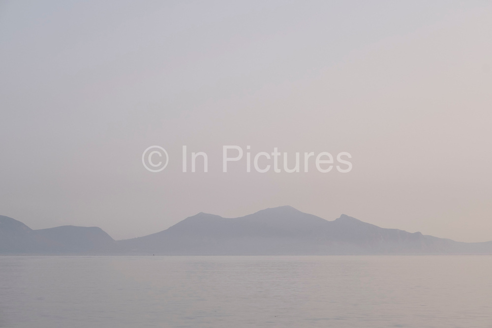 View looking across the Irish Sea towards mountains of Snowdonia National Park from Newborough Beach on 17th September 2020 in Newborough, Anglesey, Wales, United Kingdom. Known in Welsh as Llanddwyn Beach, it is a Blue Flag Beach backed by Newborough National Nature Reserve and forest on the south-western tip of Anglesey.