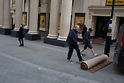 Carpet fitters roll-up a new carpet again after trimming it in the street for the interior of the Lyceum Theatre on Wellington Street, on 5th March 2019, in London, England.