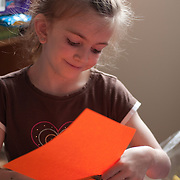 8 year old girl cuts orange paper for a home arts & crafts project