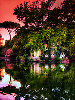"""""""Panoramic sunset reflections of Villa Borghese – Rome""""…<br /> <br /> Villa Borghese in Roma is a famous Gardens and Museum begun in the early 17th century, highlighted by a """"Temple of Aesculapius"""" at the garden lake. The Temple is located in the gardens of Borghese in Roma and was styled in the ionic characteristic by Antonio Asprucci. The temple was perhaps built-in memory of the destroyed ancient temple to the god of Medicine on Tiber Island. The temple houses a statue of Aesculapius believed to be originally from the Mausoleum of Augustus.  Neglected over the centuries, it was restored by Vincenzo Pacetti and sold to Marcantonio Borghese IV in 1785. Stretching from above Piazza del Popolo to the top of Via Veneto, Villa Borghese crowns Rome in a glorious canopy of Green. Despite the onward march of the years and extensive developmental changes to Rome, Villa Borghese has remained a perennial and pleasant space, diluting the impact of an otherwise ever-expanding urban Metropolis. The Park was originally a private vineyard, redesigned and enlarged in 1605 to grandiose proportions for Pope Paul V's nephew, the Cardinal Scipione Borghese. However, it was named after the Borghese family on the condition that it boasted the most luxurious and magnificent dwelling in Rome. Visiting the very spaciously plush park and lovely atmosphere of tall secluding lavish trees, blissful gardens, and colorful reflective lakes, one is taken away from the city life and transported to a serene country paradise. Peace and relaxation encompass the body and soul and gives time and rumination of the historical and religious world capital which is the ever Eternal City of Roma."""