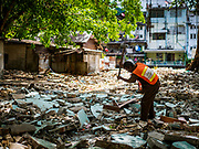 20 MARCH 2017 - BANGKOK, THAILAND: A city worker uses a sledge hammer to break up the floor of what used to be a home in Pom Mahakan. The family who lived there was evicted and the home torn down. The final evictions of the remaining families in Pom Mahakan, a slum community in a 19th century fort in Bangkok, have started. City officials are moving the residents out of the fort. NGOs and historic preservation organizations protested the city's action but city officials did not relent and started evicting the remaining families in early March.               PHOTO BY JACK KURTZ