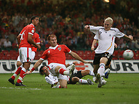 Photo: Rich Eaton.<br /> <br /> Wales v Germany. UEFA European Championships Qualifying. 08/09/2007. Germany's Bastian Schweinsteiger (R) has his shot blocked by Wales' James Collins.